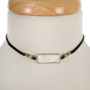 """Black faux suede choker with a howlite stone and gold tone accents. Approximately 12"""" in length."""