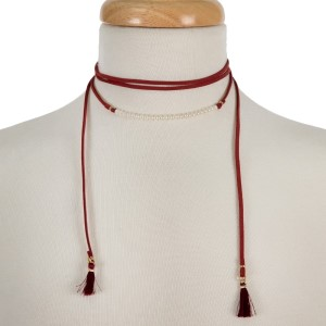 """Crimson, faux leather wrap necklace with pearl beads and fabric tassels on the ends. Approximately 60"""" in length."""