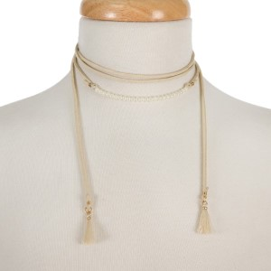 """Ivory, faux leather wrap necklace with pearl beads and fabric tassels on the ends. Approximately 60"""" in length."""