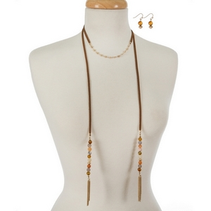 """Faux brown suede choker and wrap necklace displaying neutral colored natural stone beads and gold tone tassels. Approximately 12"""" and 40"""" in length."""