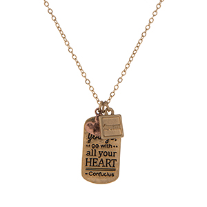 "Dainty gold tone necklace featuring a pendant stamped with ""Wherever you go, go with all your heart"" and accented with two small charms. Approximately 16"" in length."