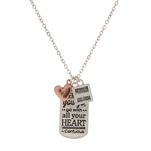 """Dainty silver tone necklace featuring a pendant stamped with """"Wherever you go, go with all your heart"""" and accented with two small charms. Approximately 16"""" in length."""