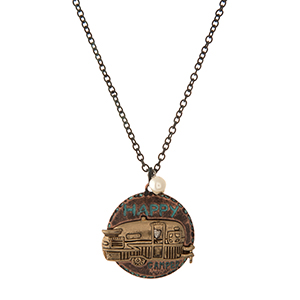 "Gold and patina tone necklace with a circle pendant stamped with ""Happy Camper."" Approximately 18"" in length."