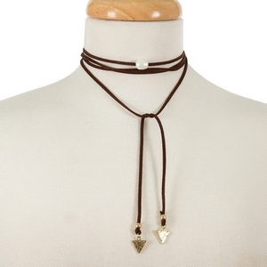 "Brown faux suede wrap necklace with a freshwater pearl bead focal and gold tone triangle shapes on the ends. Approximately 64"" in length."