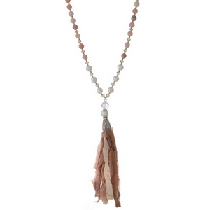 """Silver tone necklace featuring rose quartz beads and a peach fabric tassel. Approximately 33"""" in length."""