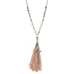 """Burnished silver tone necklace with white natural stone beads, a neutral fabric tassel and a cross pendant. Approximately 36"""" in length."""