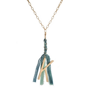 """Matte gold tone necklace featuring a teal, mint green and blue fabric tassel and a block """"K"""" initial. Approximately 33"""" in length."""