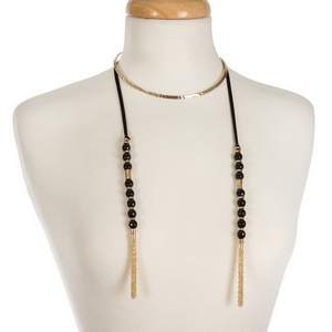 """Gold tone open metal choker featuring black faux suede pieces with black natural stone beads and chain tassels. Approximately 16"""" in length."""
