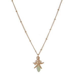 "Dainty gold tone necklace featuring a starfish pendant, accented with a pale green and freshwater pearl bead. Approximately 16"" in length."