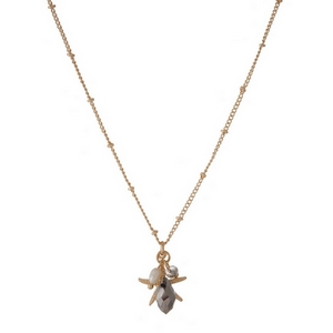 "Dainty gold tone necklace featuring a starfish pendant, accented with a hematite and freshwater pearl bead. Approximately 16"" in length."