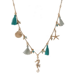 "Gold tone necklace featuring sea life charms and mint green and turquoise tassels. Approximately 16"" in length."