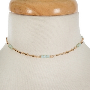 """Dainty gold tone choker featuring mint green faceted beads. Approximately 13"""" in length."""