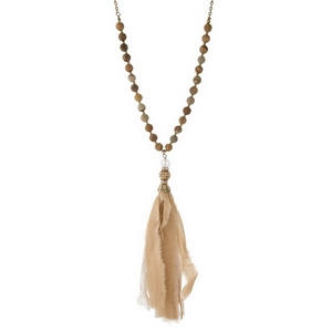 "Gold tone necklace displaying picture japser beads and a neutral tassel. Approximately 30"" in length."