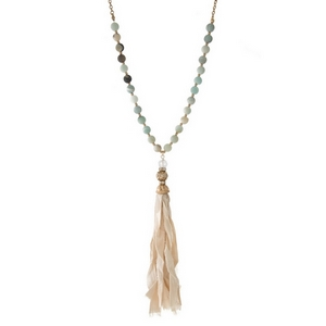 "Gold tone necklace displaying amazonite beads and an ivory tassel. Approximately 30"" in length."