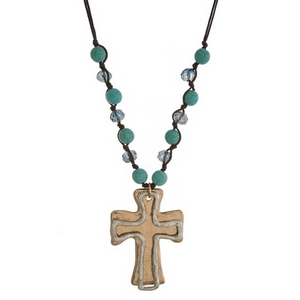 """Brown cord necklace with turquoise beads and a gold tone cross pendant. Approximately 32"""" in length."""