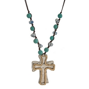 """Brown cord necklace with turquoise beads and a silver tone cross pendant. Approximately 32"""" in length."""