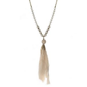 "Burnished gold tone necklace featuring an ivory fabric tassel pendant and iridescent beads. Approximately 32"" in length."