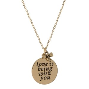 """Dainty gold tone necklace featuring a double sided pendant, stamped with """"Love is being with you"""" on one side. Approximately 16"""" in length."""
