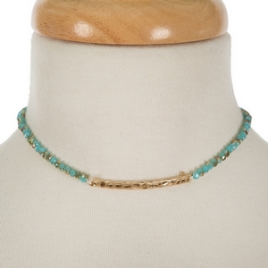 """Gold tone, dainty choker featuring turquoise faceted beads and a hammered bar focal. Approximately 12"""" in length."""
