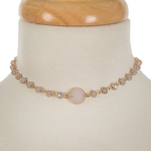 """Gold tone and gray beaded choker featuring a white faux druzy stone focal. Approximately 12"""" in length."""
