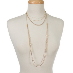 """Gold tone multi layer necklace featuring pale peach and freshwater pearl beads. Approximately 16"""" to 36"""" in length."""