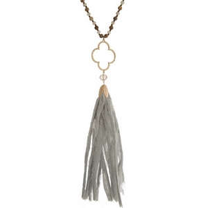 """Brown knotted cord necklace featuring gray faceted beads, picture jasper natural stone beads, an open clover shape, and a gray fabric tassel. Approximately 34"""" in length."""