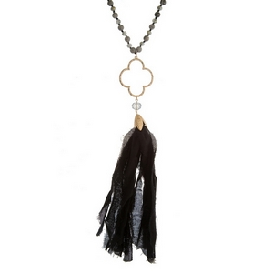 """Black knotted cord necklace featuring gray faceted beads, gray jasper natural stone beads, an open clover shape, and a black fabric tassel. Approximately 34"""" in length."""