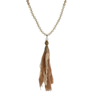 """Ivory and champagne beaded necklace with a neutral fabric tassel and gold tone accents. Approximately 32"""" in length."""