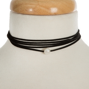 """Black faux suede wrap necklace featuring a freshwater pearl bead. Approximately 60"""" in length."""
