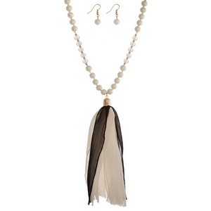 """Pearl and clear beaded necklace with a black and ivory fabric tassel. Approximately 36"""" in length."""