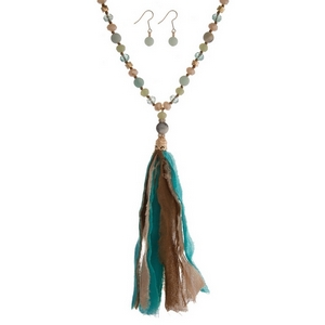 """Mint green natural stone and faceted bead necklace with a turquoise and brown fabric tassel. Approximately 32"""" in length."""