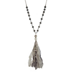 """Burnished silver tone necklace with gray natural stone beads, a gray fabric tassel and a cross pendant. Approximately 36"""" in length."""