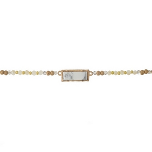 """Gold tone choker with ivory, gray and white beads and a howlite stone focal. Approximately 12"""" in length."""