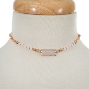 """Peach and pale pink beaded choker with a rose quartz stone focal. Approximately 12"""" in length."""