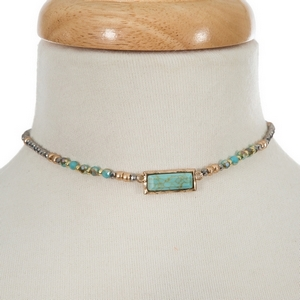 """Gold tone choker with turquoise and gray beads and a turquoise stone focal. Approximately 12"""" in length."""