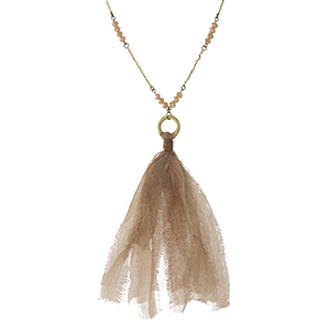 """Burnished gold tone necklace with champagne beads and a fabric tassel pendant. Approximately 32"""" in length."""