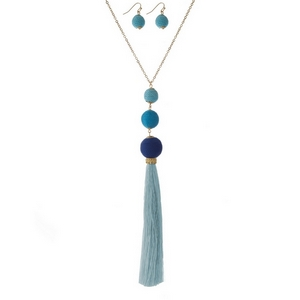 """Gold tone necklace set with blue ombre, thread wrapped beads, a thread tassel and matching fishhook earrings. Approximately 32"""" in length."""