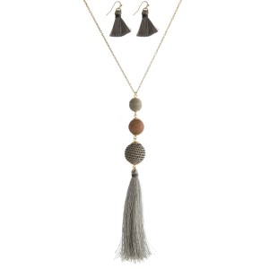 "Gold tone necklace set with a wooden bead, gray thread wrapped ball bead, and a thread tassel. Approximately 30"" in length."