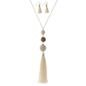 "Gold tone necklace set with a wooden bead, ivory thread wrapped ball bead, and a thread tassel. Approximately 30"" in length."
