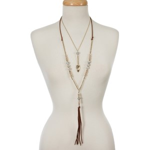 """Gold tone two layer necklace with taupe beads, natural stone, an arrowhead pendant and a faux suede tassel. Approximately 18"""" and 32"""" in length."""