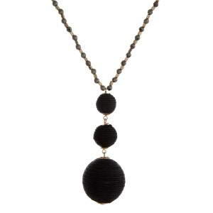 """Gold tone necklace with a black thread wrapped ball pendant. Approximately 30"""" in length."""