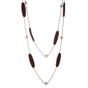 "Gold tone two layer necklace with burgundy wooden beads and clear faceted bead accents. Approximately 24"" and 32"" in length."