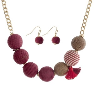 """Gold tone necklace set with burgundy thread wrapped beads and a tassel accent. Approximately 16"""" in length."""