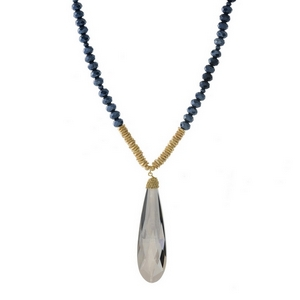 "Navy blue beaded necklace with a faceted stone pendant and gold tone accents. Approximately 32"" in length."