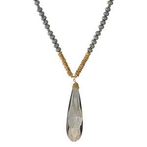"Opaque gray beaded necklace with a faceted stone pendant and gold tone accents. Approximately 32"" in length."