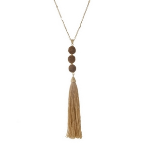 """Gold tone necklace with a beige fabric tassel and three thread wrapped beads. Approximately 30"""" in length."""
