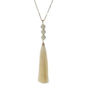 """Gold tone necklace with an ivory fabric tassel and three thread wrapped beads. Approximately 30"""" in length."""