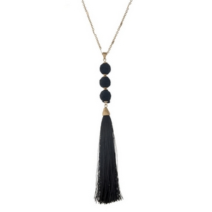 """Gold tone necklace with a black fabric tassel and three thread wrapped beads. Approximately 30"""" in length."""