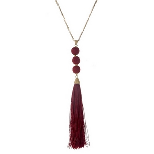 """Gold tone necklace with a burgundy fabric tassel and three thread wrapped beads. Approximately 30"""" in length."""