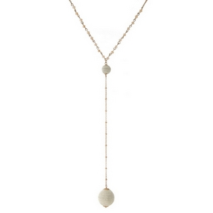 """Gold tone 'Y' necklace with ivory beads and a thread wrapped bead pendant. Approximately 26"""" in length."""